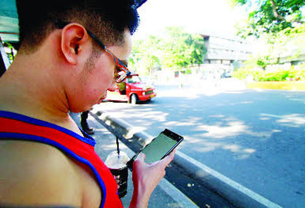 A man checks the internet connection of his mobile phone.  Starting August  free internet will be available in some public places in Cebu.  Kristine Joyce W. Campaña