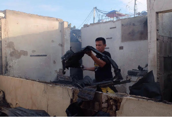 A man lifts a piece of what was left of his house in Barangay Duljo-Fatima as he searches for belongings that may have been spared by the massive fire that hit the barangay Thursday night. Jay Rommel Labra