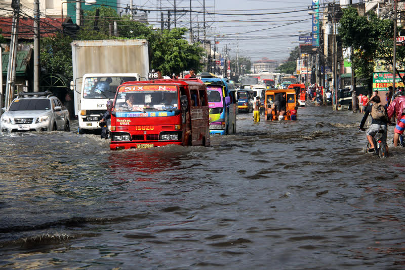 Vehicles navigate through floodwaters in Barangay Tipolo, Mandaue City following a downpour. Joy Torrejos, file