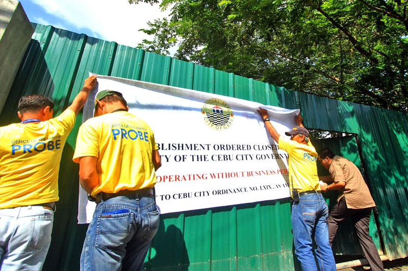 Members of the Prevention, Restoration, Beautification, and Enhancement (PROBE) of the Cebu City government put up a sign at the commissary of Rico's Lechon in Barangay Talamban, which says that the facility has been ordered closed for operating without a business permit. Aldo Nelbert Banaynal