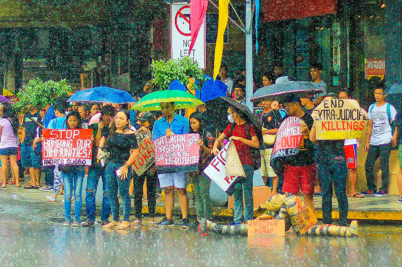 A handful of students stay undeterred by the downpour in Cebu City yesterday as they protest government's action on controversial issues, including the ongoing war against illegal drugs. Aldo Nelbert Banaynal