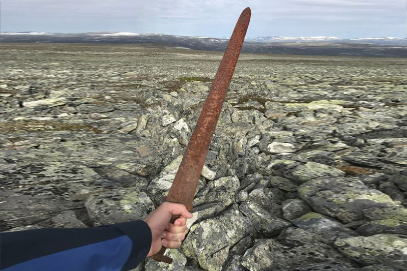 Einar Ambakk, one of the hunters that found an ancient Viking sword slid down between rocks during a reindeer hunt, raises it in Lesja, some 275 kilometers (170 miles) north of Oslo. According to a Norwegian archeologist, the nearly 1-meter-long (3-foot) sword dating from about 850-950 A.D. may have been left by a person who got lost in a blizzard and died on the mountain from exposure. Einar Ambakk via AP