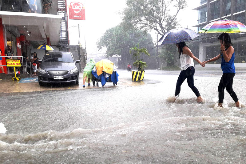 Two women cross a flooded street in Barangay Mabolo, Cebu City at the height of the downpour Monday morning. Aldo Nelbert Banaynal