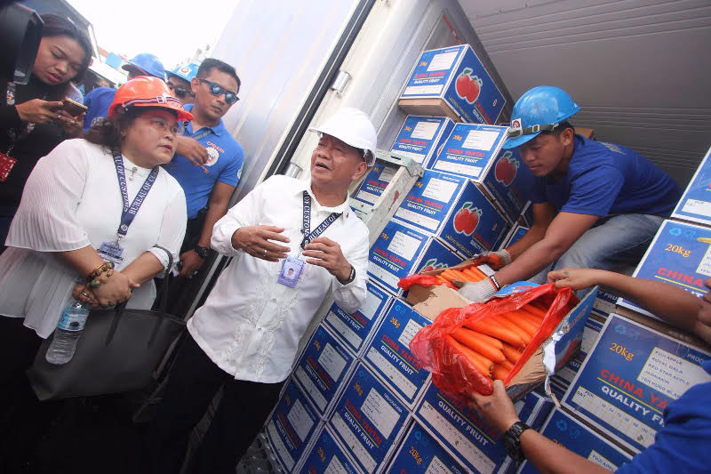 Customs Commissioner Isidro Lapeña (center) opens a container van that contained shipment that is reportedly undervalued. Lapeña has vowed to stop smuggling at the Cebu port. Joy Torrejos