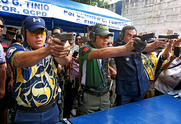 PNP chief Director General Ronald dela Rosa (left) leads the ceremonial firing at the first 'Chief PNP Bato Cup' shooting competition held in honor of his birthday at Camp Karingal yesterday. Joining him are SAF director Chief Supt. Benjamin Lusad and QCPD director Chief Supt. Guillermo Eleazar. BOY SANTOS