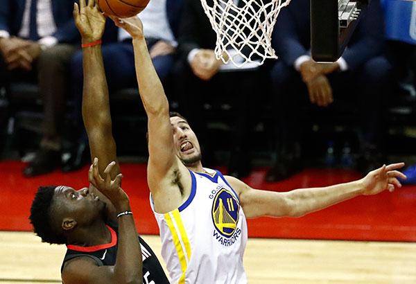 Nag-unahan sa pagkuha ng rebound sina Warriors guard Klay Thompson at Rockets center Clint Capela.