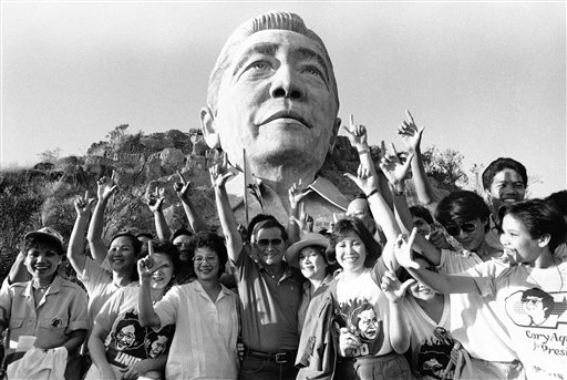 "In this Jan. 2, 1986 file photo, opposition presidential candidate Corazon Aquino, third from left, her vice presidential running mate Salvador Laurel and supporters flash the traditional ""L"" sign for Laban, meaning ""Fight!"" as they stopped briefly at President Ferdinand Marcos' giant bust on Marcos Park in Ilocos. They held campaign rallies earlier at Marcos' Ilocos region. AP/Alberto Marquez"