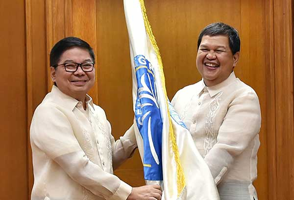 CHANGING OF THE GUARD: Former central bank governor Amando Tetangco (left) officially turns over the BSP flag to his successor Nestor Espenilla.