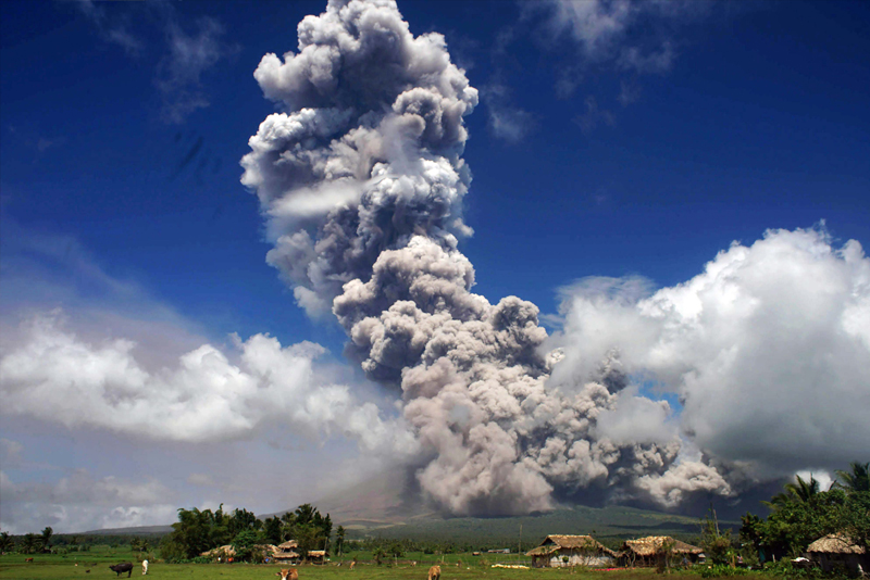 A giant column of ash rises into the air from Mayon Volcano in Legazpi City, Albay yesterday, darkening the skies in several communities. Phivolcs raised the Mayon threat level to 4 yesterday, warning of an imminent 'hazardous eruption.' AFP