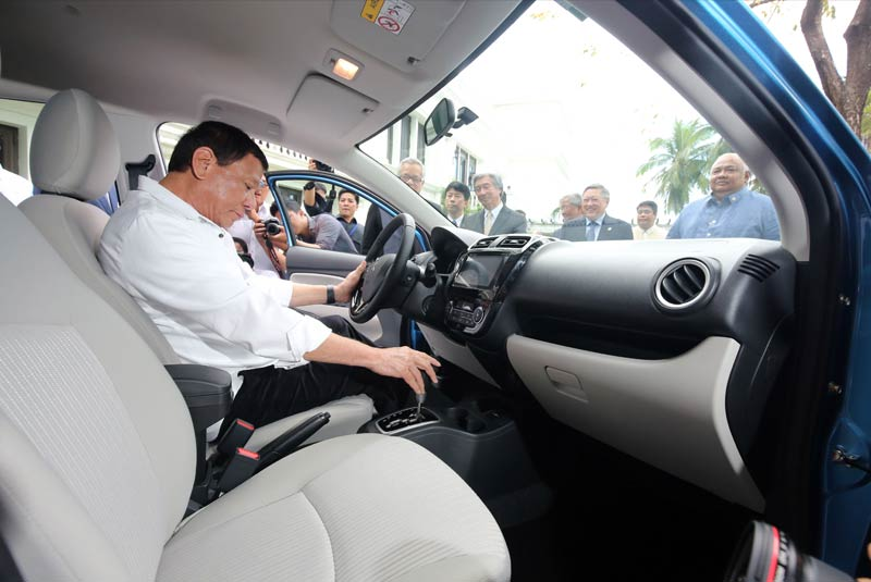 From Presiden President Duterte tries out the controls of the first locally assembled Mitsubishi Mirage G4