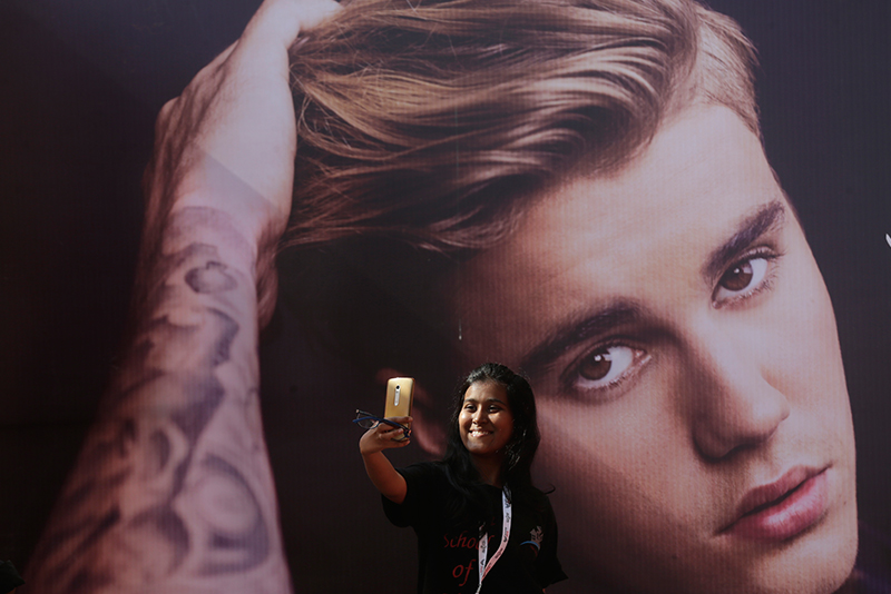 A fan of Canadian singerJustin Biebertakes a selfie in front of his poster ahead of a concert by him in Mumbai, India, Wednesday, May 10, 2017. Rafiq Maqbool/AP Photo
