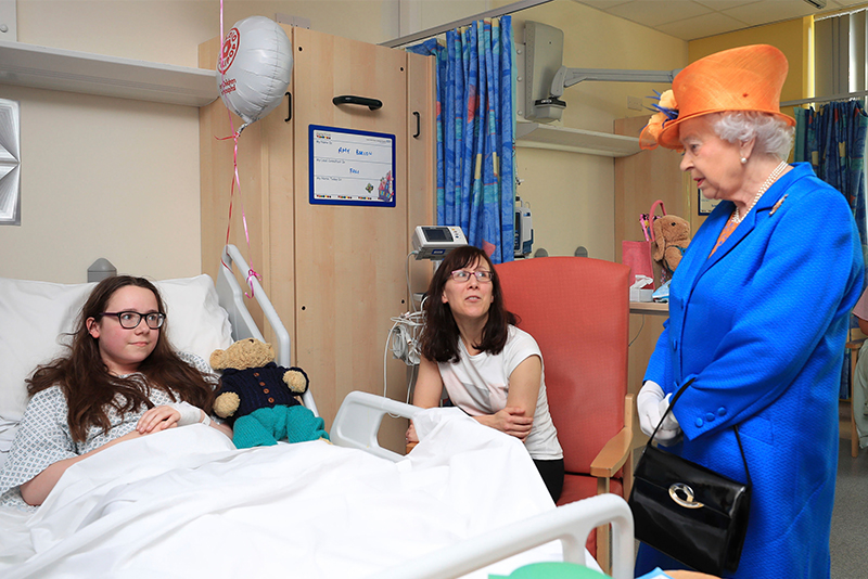 Britain's Queen Elizabeth II, right, speaks to Amy Barlow, 12, from Rawtenstall, Lancashire, left, and her mother, Kathy, as she visits the Royal Manchester Children's Hospital in Manchester England, to meet victims of the terror attack in the city earlier this week and to thank members of staff who treated them Thursday May 25, 2017.Pool via AP/Peter Byrne