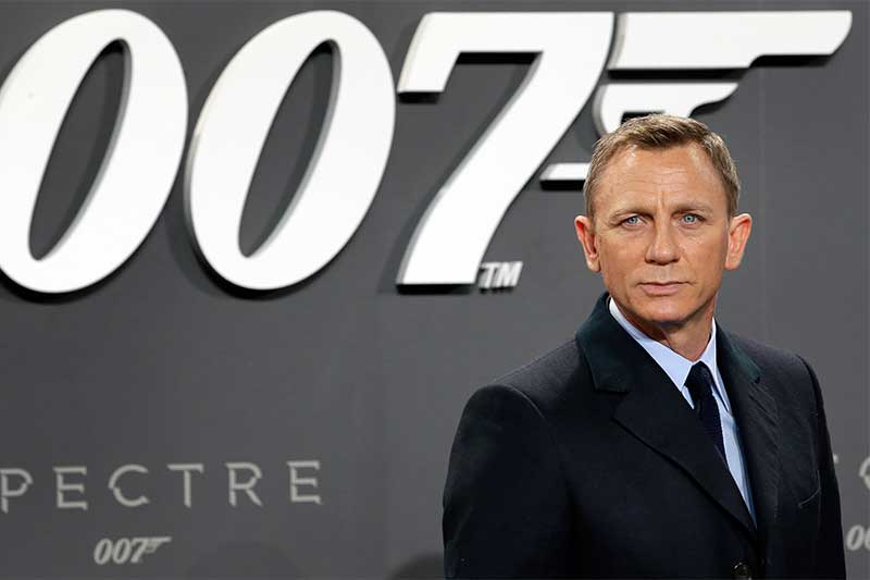 "FILE - This is a Wednesday, Oct. 28, 2015 file photo of actor Daniel Craig poses for the media as he arrives for the German premiere of the James Bond movie 'Spectre' in Berlin, Germany. British actor Daniel Craig announced he returning to cars, cocktails and camera pens to play James Bond in the franchise's next film, due out in 2019. The 49-year old actor told Stephen Colbert on Tuesday night's ""Late Show"" that it will likely be his last time playing 007, and that he hopes to ""go out on a high note."" AP/Michael Sohn/File"