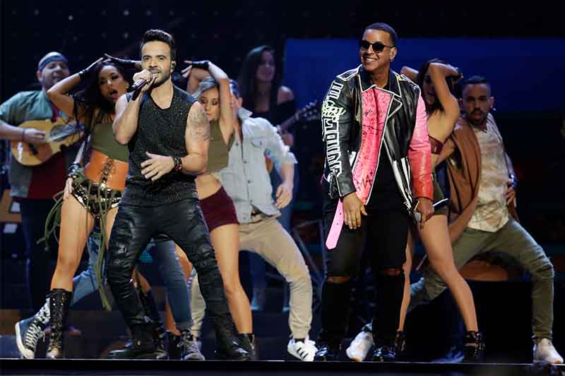"""FILE - In this April 27, 2017 file photo, singers Luis Fonsi, left and Daddy Yankee perform during the Latin Billboard Awards in Coral Gables, Fla. The ubiquitous hit song """"Despacito"""" has tied Mariah Carey's 16-week record at No. 1 on the Billboard Hot 100 chart. Billboard announced Monday, Aug. 28, that Luis Fonsi's song and Carey's duet with Boyz II Men, """"One Sweet Day,"""" are the longest-running No. 1 songs in the 59-year history of the charts. AP/Lynne Sladky, File"""