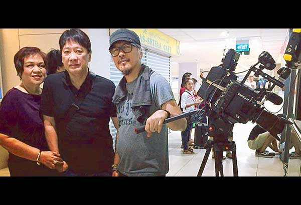 The fresh look of Lav Diaz (right) during the shoot of Henrico's Farm at Singapore's Lucky Plaza with frequent Lion City visitors Simon Santos and wife Glo dropping in. — Photos courtesy of Simon Santos of Video 48