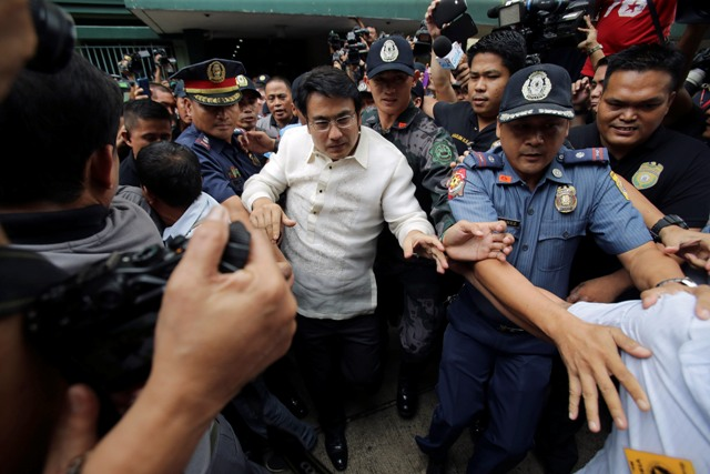 Sen. Ramon Revilla Jr., center, a popular actor accused of receiving 224 million pesos ($5.1 million) in kickbacks from a scam that allegedly diverted millions of dollars from anti-poverty and development funds allotted to lawmakers' pet projects, is escorted by police after attending his arraignment at the Sandiganbayan anti-graft court in suburban Quezon City, Philippines on Thursday, June 26, 2014. AP/Aaron Favila