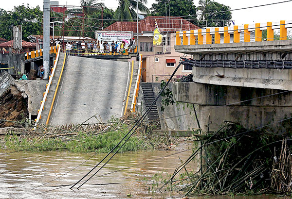 Residents survey a damaged Calumpang bridge in Batangas City yesterday. The bridge, which connects two barangays of the city, collapsed at the height of Typhoon Glenda. EDD GUMBAN