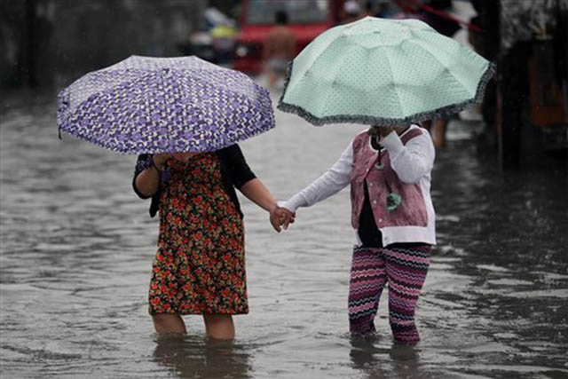 Filipino women hold hands as they negotiate floodwaters from a swollen creek in the coastal village of Malabon on Wednesday, July 8, 2015. AP/Aaron Favila
