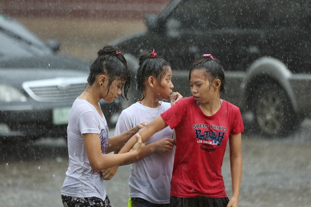 Filipino girls walk together in the heavy rains in Manila, Philippines Sunday, Sept. 13, 2015. Heavy downpours have frequented the metropolis almost daily causing traffic jams and floods in some areas. AP/Aaron Favila