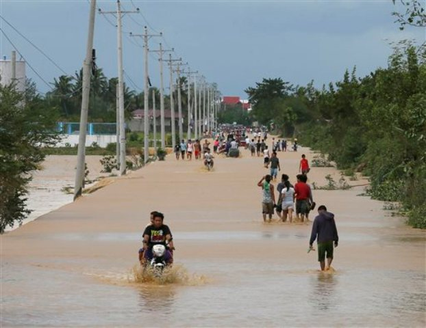 """Residents wade through floodwaters brought about byTyphoon """"Lando""""at Zaragosa township, Nueva Ecija on Monday, Oct. 19, 2015. AP/Bullit Marquez"""