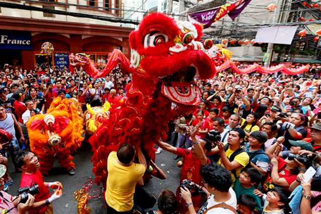 Dragon and lion dancers perform before a huge crowd in celebration of the Chinese Lunar New Year Monday, Feb. 8, 2016 at Manila's Chinatown district in Manila, Philippines. This year is Year of the Monkey in the Lunar calendar.AP/Bullit Marquez