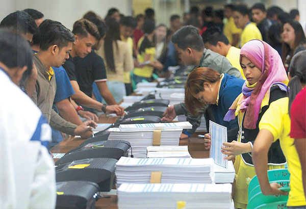 Workers test vote counting machines using demo ballots at the National Printing Office in Quezon City yesterday. MICHAEL VARCAS