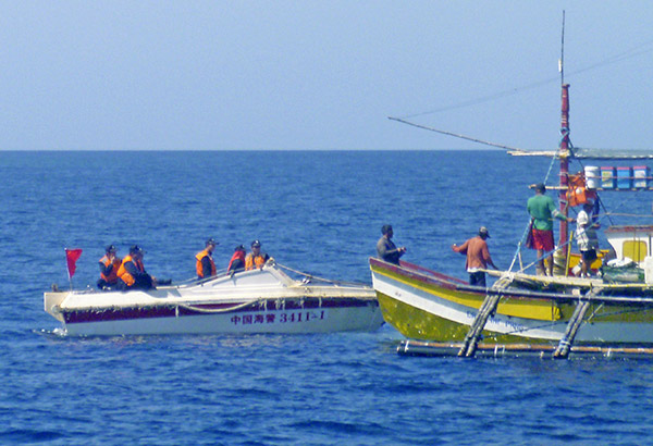 In this Feb. 27, 2015 photo provided by fisherman Renato Etac, Chinese Coast Guard members approach his fellow fishermen near Panatag (Scarborough) Shoal in the West Philippine Sea. More than once, the Chinese approached Etac's boat and pointed their rifles at him, but he says he knew they would not fire and start a war. AP, File
