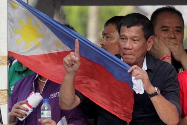 Presidential candidate Mayor Rodrigo Duterte holds a Philippine flag while flashing the Number 1 sign as his campaign motorcade makes its way through the streets of Malabon, Philippines, Wednesday, April 27, 2016. The tough-talking Duterte, the mayor of the southern Philippine city of Davao, is the front-running candidate leading to the May 9 presidential elections. AP/Bullit Marquez