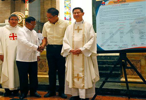 """Presidential candidates Vice President Jejomar Binay, second from left, and Mar Roxas, second from right, shake hands as they pose with Manila Archbishop Cardinal Luis Antonio Tagle, right, and Rev.Fr. Anton Pascual, shortly after signing the covenant for """"truthful, responsible, upright, transparent, and honest"""" elections on May 9, at the Manila Cathedral in Manila, Philippines Monday, May 2, 2016. Binay and Roxas are almost """"statistical tie"""" in recent poll surveys behind front-runner Rodrigo Duterte and Grace Poe. AP Photo/Bullit Marquez"""