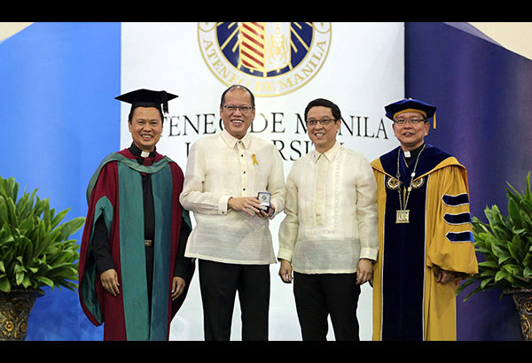 President Aquino receives a commemorative silver medal from officials of the Ateneo de Manila University led by ADMU president Fr. Jose Ramon Villarin (right) after delivering a speech during the school's graduation rites yesterday.