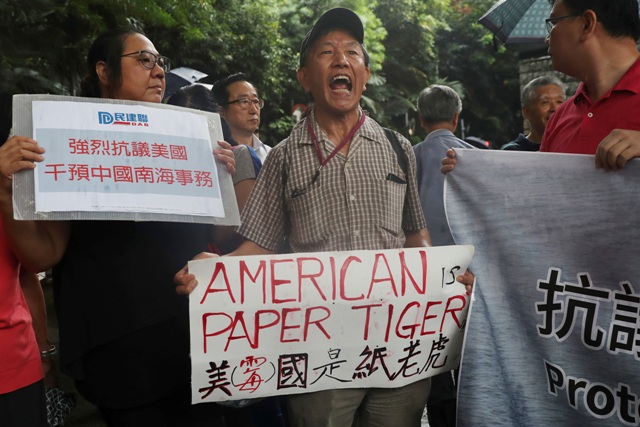 "Pro-Beijing protesters shout slogans against the United States supporting an international court ruling of the South China Sea outside the U.S. Consulate in Hong Kong, Thursday, July 14, 2016. China warned other countries Wednesday against threatening its security in the South China Sea after an international tribunal handed the Philippines a victory by saying Beijing had no legal basis for its expansive claims there. A sign, left, reads ""Strongly protest against U.S. intervention in South China Sea Affairs."" AP/Kin Cheung"