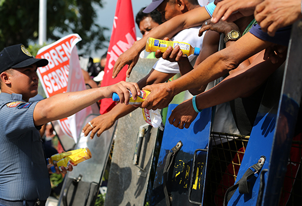 A policeman gives bottled juice to activists and supporters of Philippine President Rodrigo Duterte during a rally near the gates of the House of Representatives in suburban Quezon city, north of Manila, Philippines on Monday, July 25, 2016. President Duterte delivered his first State of the Nation Address yesterday. AP Photo/Aaron Favila