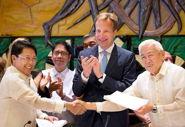 Luis Jalandoni of the National Democratic Front (right) shakes hands with Labor Secretary Silvestre Bello following the signing an indefinite ceasefire deal yesterday. Looking on is Norway's Minister of Foreign Affairs Boerge Brende. AP