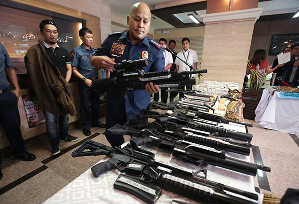 PNP chief Director General Ronald dela Rosa examines one of the high-powered firearms seized from suspected Sayyaf arms supplier Unding Kenneth Isa (left) who was presented to media at Camp Crame on Tuesday. The guns and ammunition were seized from a house in Barangay West Crame in San Juan last Sept. 24. MICHAEL VARCAS
