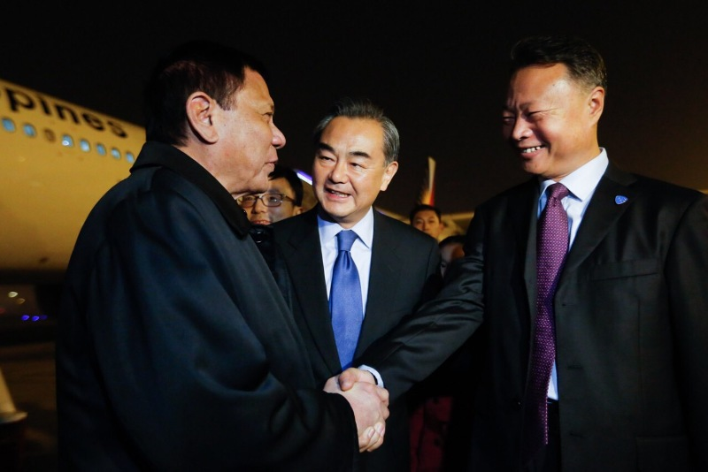 President Rodrigo Duterte shakes hands with Chinese Ambassador to the Philippines Zhao Jianhua as he arrives in China for a four-day state visit. Also in the photo is Chinese Foreign Minister Wang Yi. Presidential Photo/Released, file