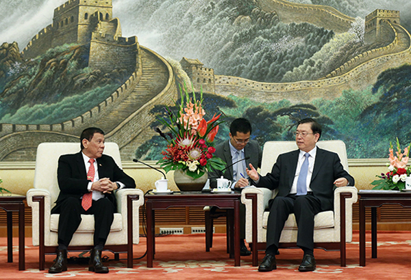 President Duterte listens to Zhang Dejiang, chairman of the Standing Committee of the National People's Congress of China, during a meeting in Beijing on Thursday. AP