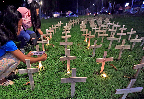 In this Nov. 8, 2016 photo, families light candles and offer prayers for victims of Yolanda in Fatima Village, Tacloban City. EDD GUMBAN, File