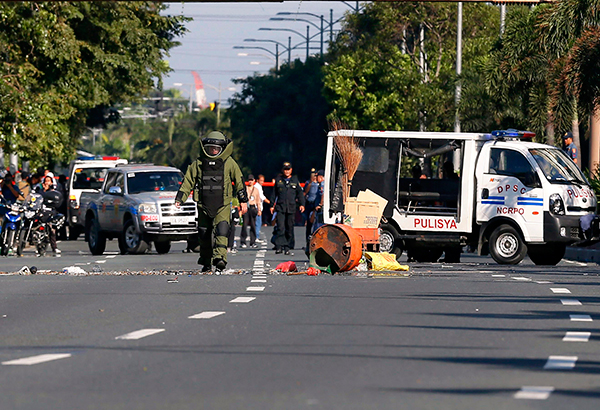 A member of the Manila Police District bomb squad approaches the remnants of a package containing an improvised explosive device that was safely detonated along Roxas Boulevard in Manila on November 28. AP, file