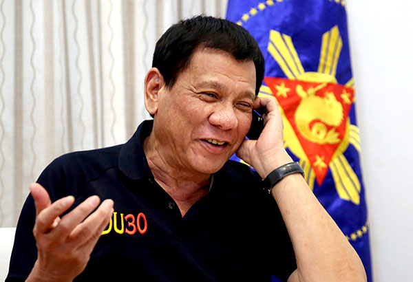GOOD RAPPORT: President Duterte is all smiles as he talks to US president-elect Donald Trump on the phone at the Legaspi Suites in Davao City the other night. During the seven-minute phone conversation, Trump told Duterte the Philippines was conducting its deadly drug war 'the right way.'