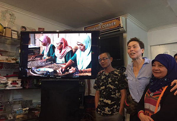 A Facebook post of Amor Maclang shows (from left) Muddazer Hailanie, chairman of the Kankitap Consumers Cooperative, yoga teacher Rina Ortiz and Mercia Alli of Matawkasi Inc., a communitybased organization in Sulu beside a video presentation of 'Salamat' coffee production.