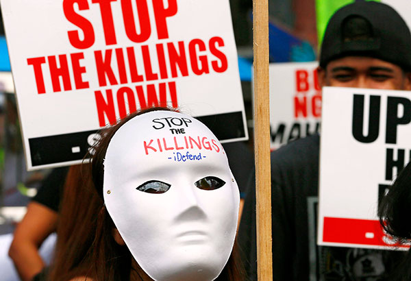 A masked protester displays a placard as they gather for a rally on Mendiola Bridge in Manila to mark International Human Rights Day yesterday. The protesters called on the government to end extrajudicial killings in the country. AP