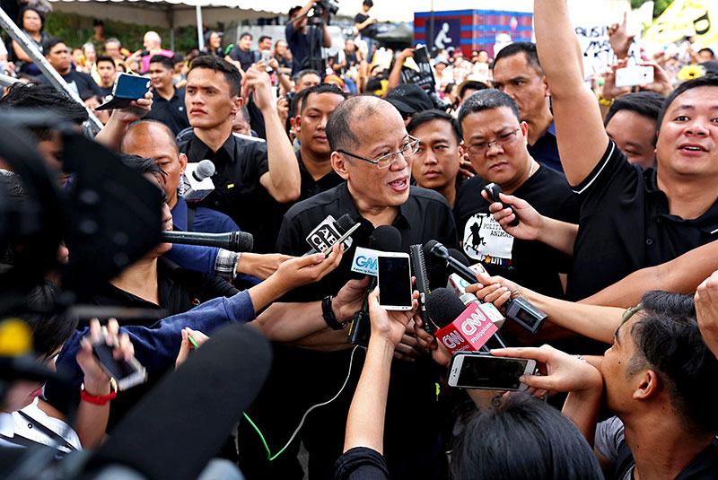 Former president Benigno Aquino III speaks to reporters at the 31st anniversary celebration of the EDSA Revolution at the People Power Monument in Quezon City yesterday.  BOY SANTOS