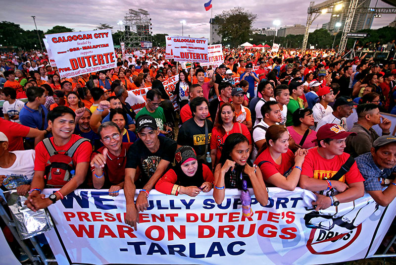 Pro-Duterte groups hold up streamers and placards to express support for the President's war on drugs, corruption and criminality during a vigil at Rizal Park yesterday.  KRIZJOHN ROSALES