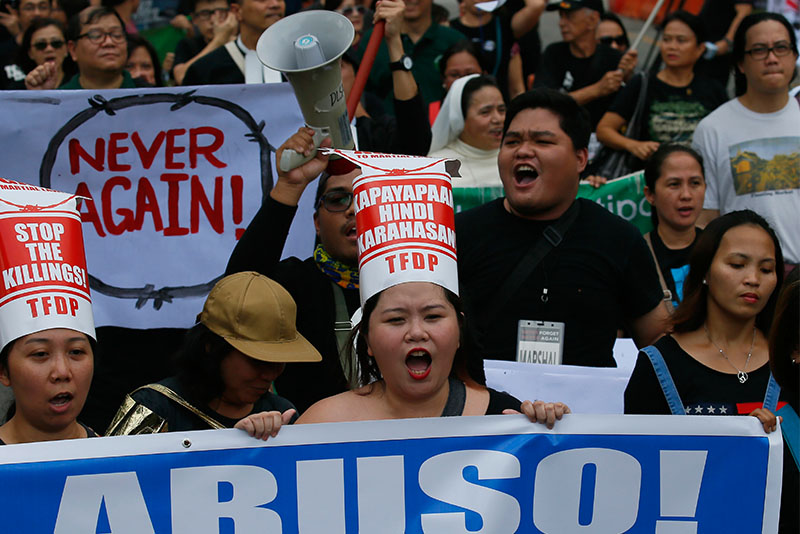 Protesters gather at the People Power Monument to mark the 31st anniversary of the near-bloodless revolt that toppled the 20-year-rule of the late dictator Ferdinand Marcos Saturday, Feb. 25, 2017, in suburban Mandaluyong city northeast of Manila, Philippines. The left-wing and pro-democracy activists warned about the current president's dictatorial tendencies and condemn his decision to allow Marcos to be buried at a heroes' cemetery. The banner reads: Abuse! AP/Bullit Marquez