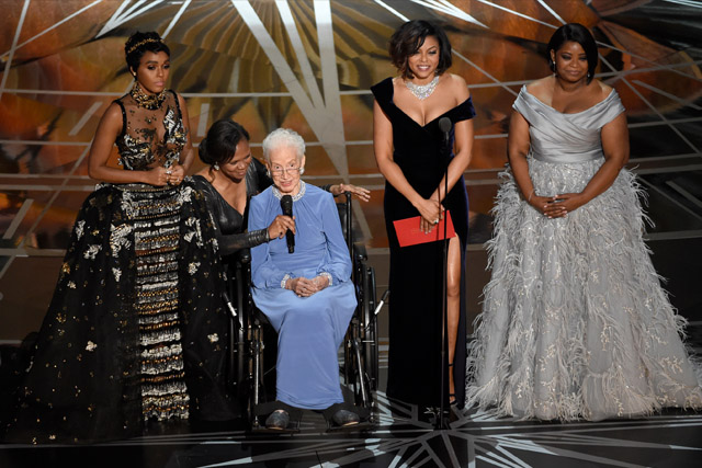 "Janelle Monae, left, Taraji P. Henson, second right and Octavia Spencer, right, introduce Katherine Johnson, seated, the inspiration for ""Hidden Figures,"" as they present the award for best documentary feature at the Oscars on Sunday, Feb. 26, 2017, at the Dolby Theatre in Los Angeles.Chris Pizzello/Invision/AP"
