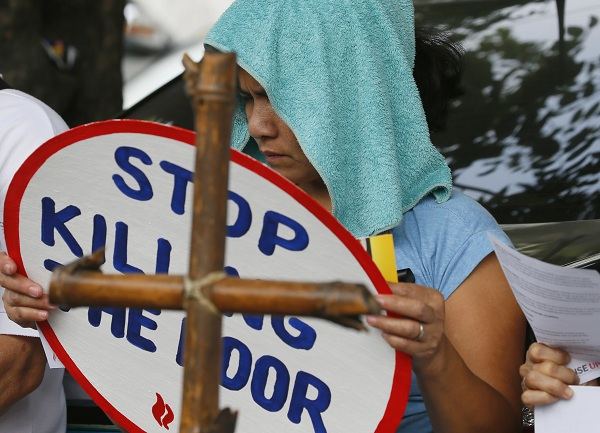 "A relative displays a ""Stop Killing The Poor"" message during a protest outside the Ombudsman building to lend support to Mary Ann D. Domingo, the widow and mother respectively of Luis Bonifacio and Gabriel Bonifacio as she files two counts of murder and administrative cases against Police Superintendent Ali Jose Duterte and at least seven other police officers in the killing last year of Luis and Gabriel Bonifacio inside their house, Tuesday, March 14, 2017 in suburban Quezon city, northeast of Manila, Philippines. The charges were one of a few cases filed against police officers by relatives since the so-called war on drugs by President Rodrigo Duterte killed more than 7,000 people in the first 8 months of his term. AP/Bullit Marquez"