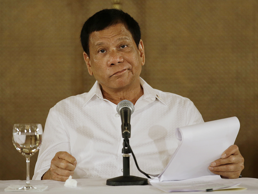 """In this Monday, March 13, 2017 file photo, Philippine President Rodrigo Duterte reacts during a press conference at the Malacanang presidential palace in Manila, Philippines. Duterte says his militarily inferior country can't stop China's actions in contested waters, responding to a reported plan by Beijing to construct an environmental monitoring station in a disputed shoal off the Philippines' northwest coast. Duterte, however, warned Sunday, March 19, that he would invoke a July 12 arbitration ruling that invalidated China's territorial claims in the South China Sea if the Chinese """"start to tinker with the entitlement,"""" apparently meaning when Beijing starts to tap the offshore area's resources. AP/Aaron Favila, File"""