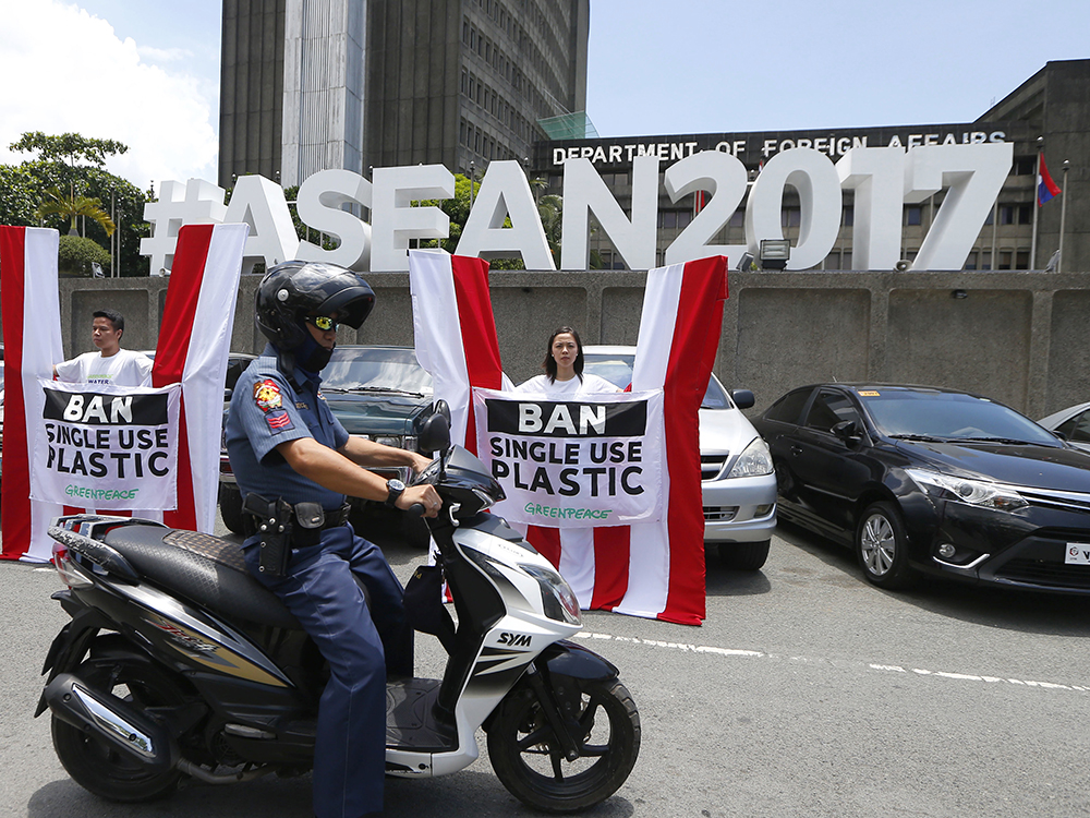 "A police officer drives his motorcycle past a couple of Greenpeace activists as they picket the Department of Foreign Affairs to relay a message to ASEAN leaders and delegates, who are to attend the April 26-29 summit, to urge the 10-member regional grouping to ban single-use of plastics and to act on plastics and marine debris pollution Tuesday, April 25, 2017 in suburban Pasay city, south of Manila, Philippines. he Philippines is hosting the summit of 10-member ASEAN (Association of Southeast Asian Nations) with the theme: Partnering for Change, Engaging the World."" AP/Bullit Marquez"