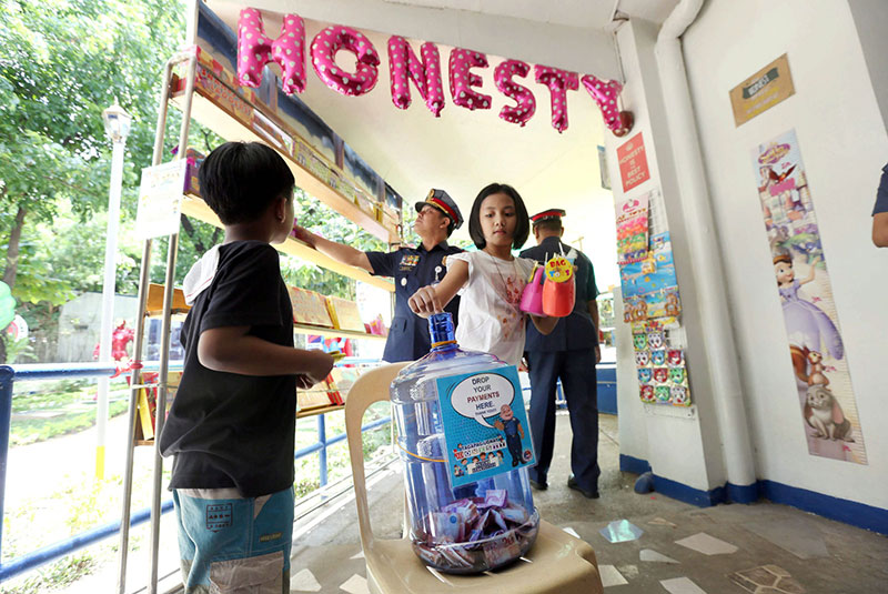 A girl drops her payment for an item she bought from the Honesty Toy Store. BOY SANTOS