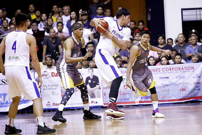 June Mar Fajardo keeps the ball out of the reach of Mark Barroca in the Mindanao vs Gilas Pilipinas PBA All Star game last night at the Xavier University Gymnasium.